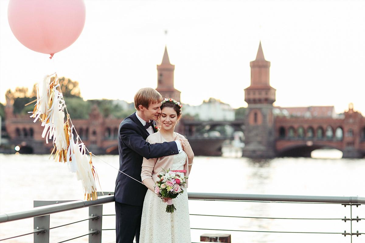 Hochzeitsfoto von Brautpaar mit rosa Luftballon bei Sonnenuntergang an der Spree vor der Oberbaumbrücke bei nhow Hotel Hochzeit in Berlin © Hochzeitsfotograf Berlin www.hochzeitslicht.de