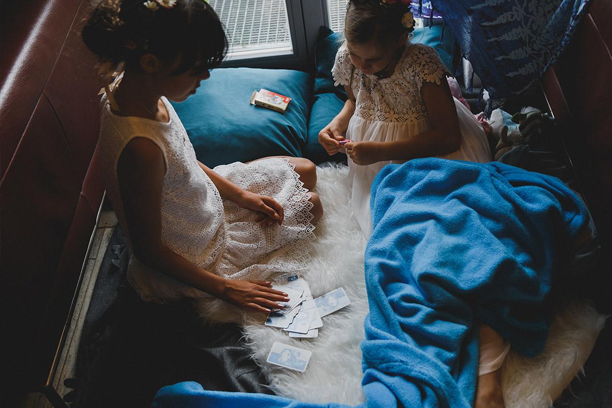 Hochzeitsreportagefoto von Blumenmädchen beim Kartenspielen während unkonventioneller Boho-Hochzeit bei Berlin © Hochzeitsfotograf Berlin www.hochzeitslicht.de