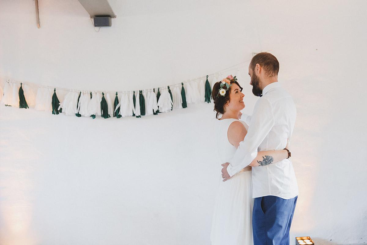 Brautpaarfoto vor schwarz-weißer Tassel-Girlande in Ferienscheune Barnimer Feldmark bei Hochzeit im Boho- und Hippiestil bei Berlin © Hochzeitsfotograf Berlin www.hochzeitslicht.de