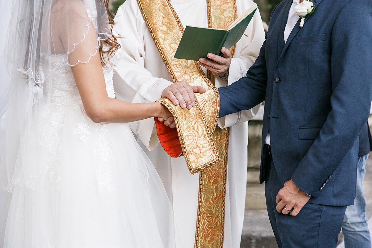 Detailfoto von Brautpaar und Pfarrer bei Trauungszeremonie im Park von Patrick Hellmann Schlosshotel Berlin Grunewald © Hochzeit Berlin www.hochzeitslicht.de