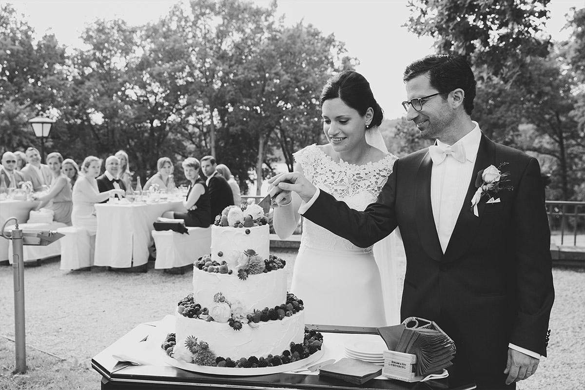 Hochzeitsreportagefoto vom Anschneiden der dreistöckigen Hochzeitstorte im Seehaus von Schoss Liebenberg © Hochzeitsfotograf Berlin www.hochzeitslicht.de