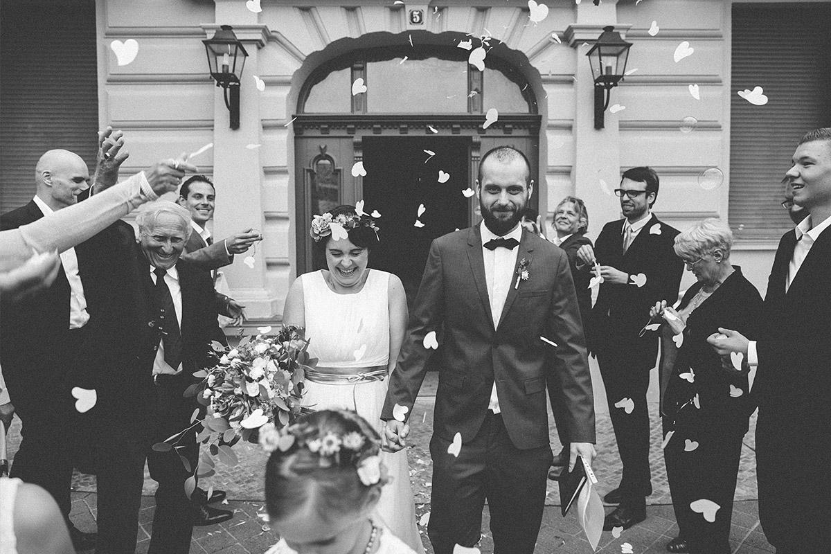 schwarz-weiß Hochzeitsfotografie vom Auszug des Brautpaares nach Trauung aufgenommen von Hochzeitsfotograf Berlin vor Standesamt Werneuchen © Hochzeitsfotograf Berlin www.hochzeitslicht.de