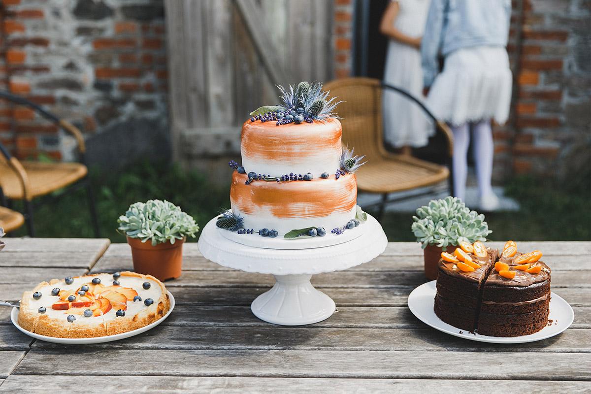 Hochzeitsfoto von Hochzeitstorte und Kuchenbuffet bei Landhochzeit in Brandenburger Scheune bei Berlin © Hochzeitsfotograf Berlin www.hochzeitslicht.de