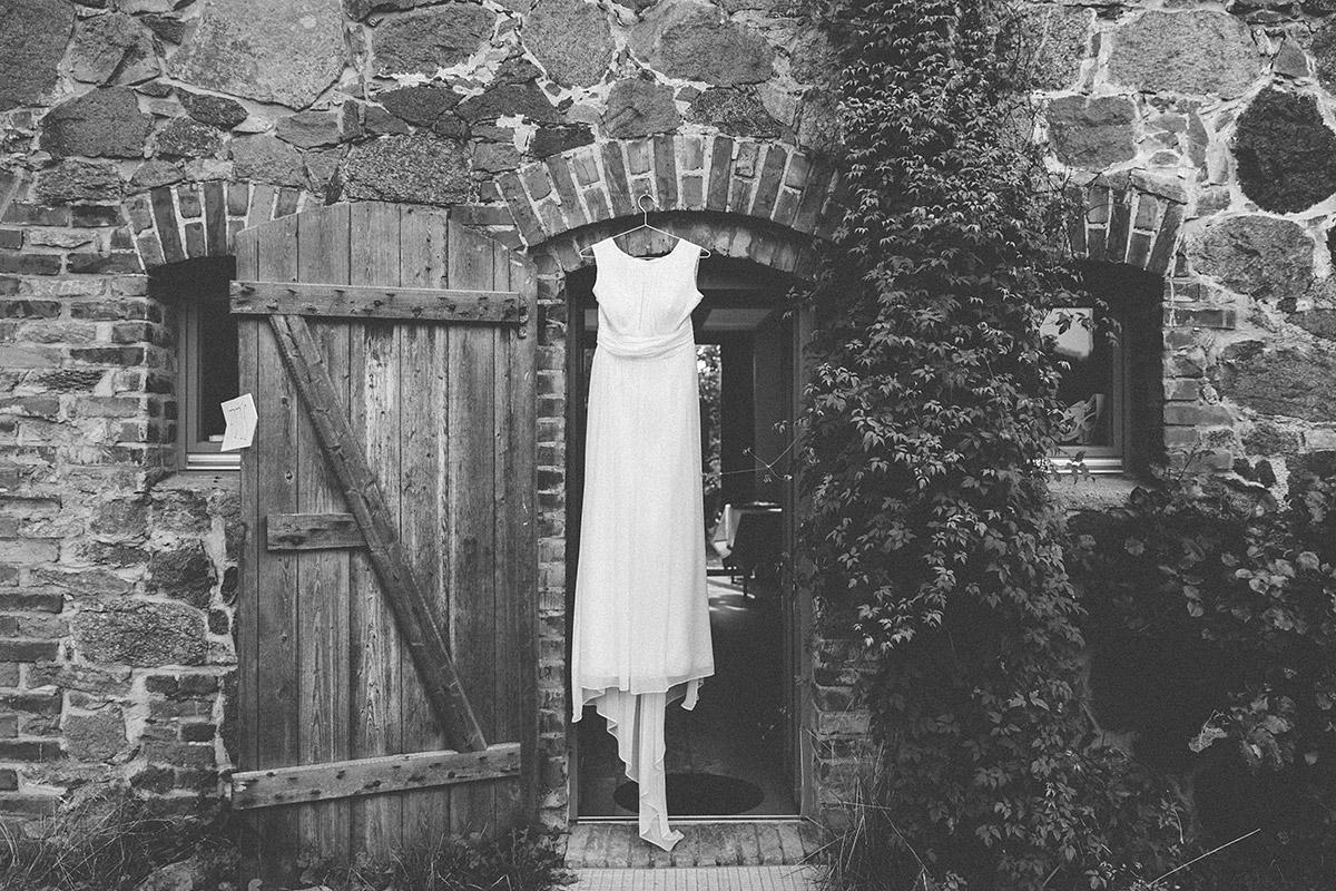 schwarz-weiß Hochzeitsfoto von Brautkleid an Eingang zu Scheune bei Landhochzeit bei Berlin in Brandenburg © Hochzeitsfotograf Berlin www.hochzeitslicht.de