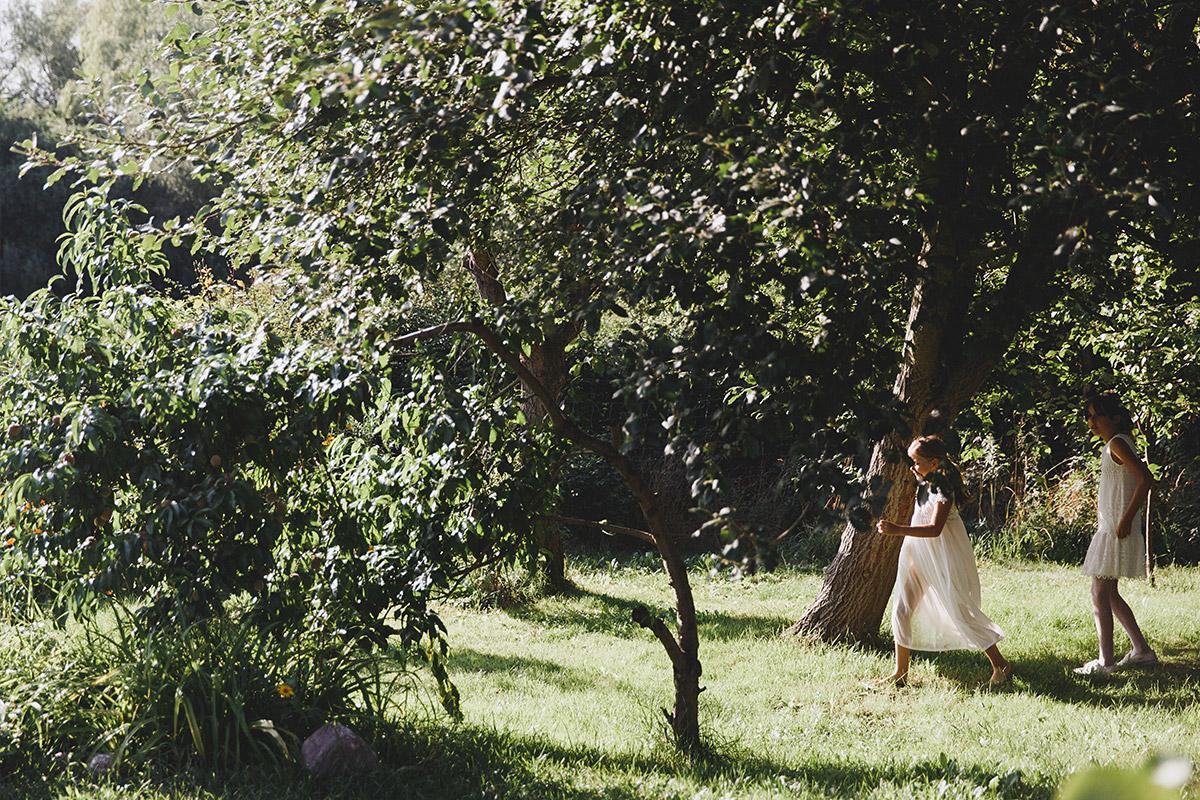 Hochzeitsreportage-Foto von spielenden Blumenmädchen im Garten von Scheune bei Landhochzeit Brandenburg © Hochzeitsfotograf Berlin www.hochzeitslicht.de