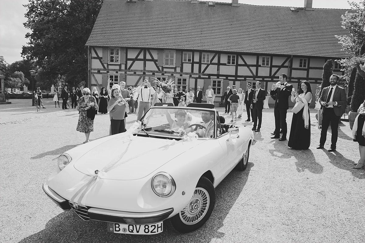 Hochzeitsfoto von Brautpaar in Hochzeitsauto bei Hochzeit auf Schloss und Gut Liebenberg © Hochzeitsfotograf Berlin www.hochzeitslicht.de