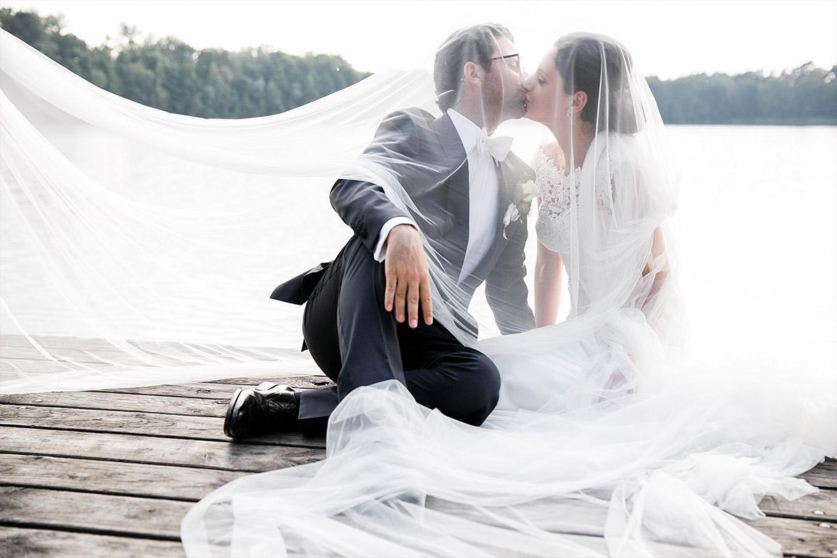 kreatives Hochzeitsfoto von Brautpaar unter Schleier am Steg vom Seehaus von Schloss und Gut Liebenberg © Hochzeitsfotograf Berlin www.hochzeitslicht.de