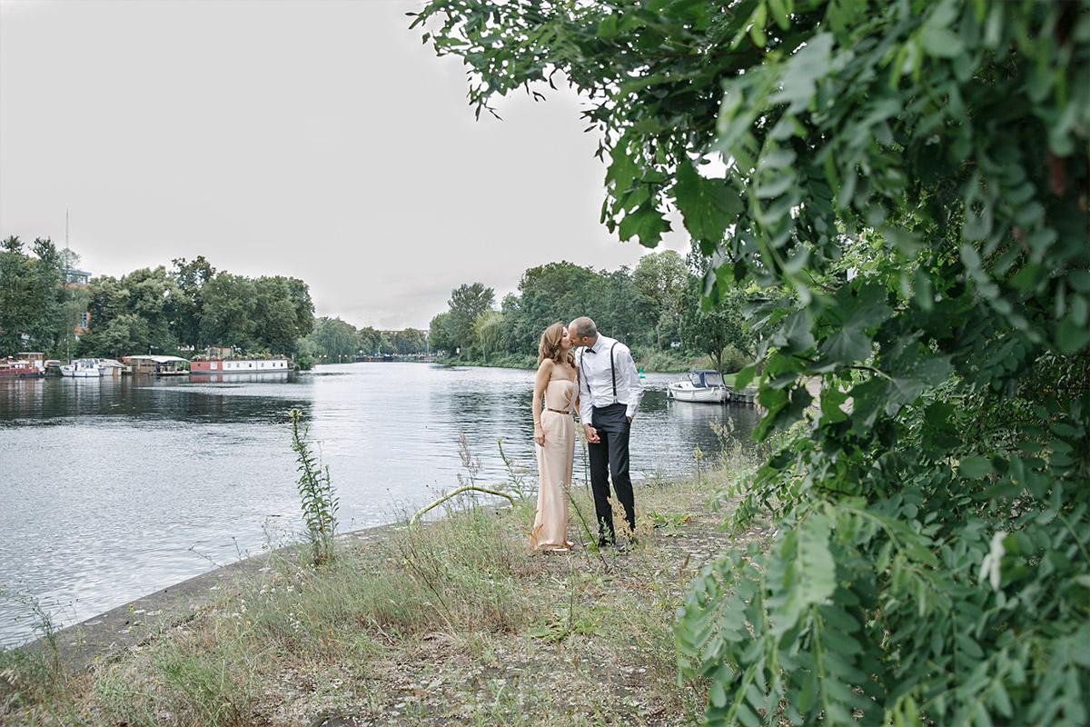 romantisches Brautpaarfoto am Wasser mit Braut in einem figurbetontem Overall von Kaviar Gauche bei Bridge Studios Berlin Hochzeit am Westhafen © Hochzeit Berlin www.hochzeitslicht.de