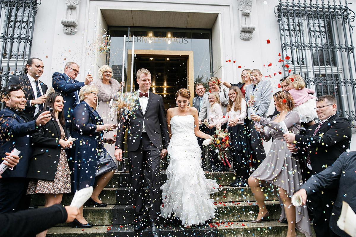 Hochzeitsfoto vom Auszug des Brautpaars, das nach freier Trauung im Ermelerhaus von Gästen mit buntem Konfetti beworfen wird, aufgenommen von Hochzeitsfotograf Berlin-Mitte © Hochzeit Berlin www.hochzeitslicht.de