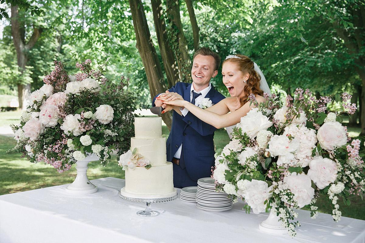 ungestelltes Hochzeitsfoto vom Anschneiden der Hochzeitstorte bei Vintage-Hochzeit im Gut Suckow Brandenburg © Hochzeitsfotograf Berlin www.hochzeitslicht.de