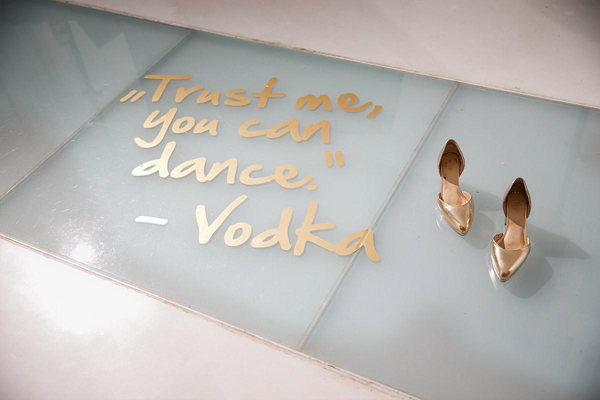 """Detailfoto von Spruch auf der Tanzfläche """"Trust me, you can dance. - Vodka"""" und goldenen Brautschuhen bei moderner Berlin-Hochzeit in Bridge Studios © Hochzeit Berlin www.hochzeitslicht.de"""