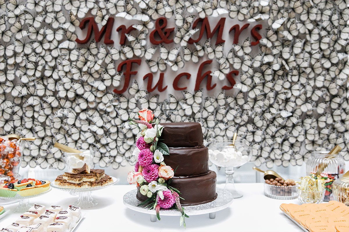 Hochzeitsfoto von DIY-Hochzeitstorte und Candybar vor Wand aus Schmetterlingen bei deutsch-russischer Hochzeit im Ermelerhaus in Berlin-Mitte © Hochzeit Berlin www.hochzeitslicht.de