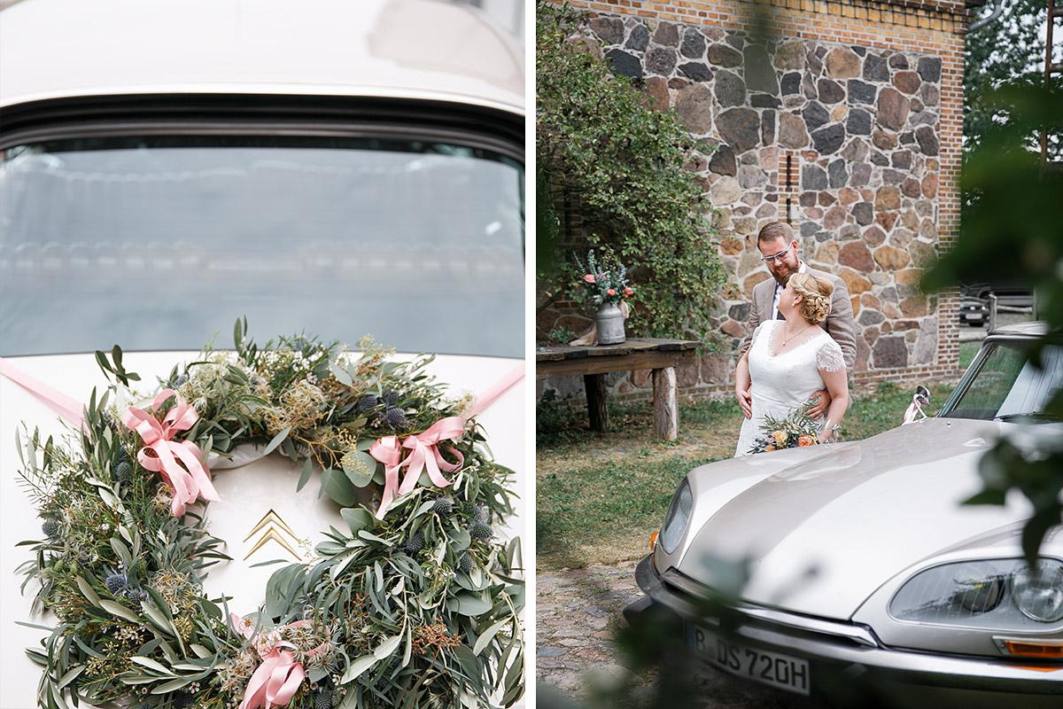 Brautpaarfoto und Detailfoto von Blumenkranz auf Hochzeitsauto bei Scheunenhochzeit in Brandenburg © Hochzeitsfotograf Berlin www.hochzeitslicht.de