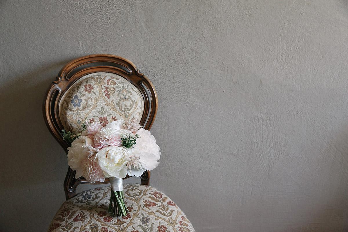 Hochzeitsfoto von Brautstrauß aus Dahlien und Pfingstrosen in Pastellfarben auf Stuhl bei Vintage-Hochzeit im Gut Suckow Brandenburg © Hochzeitsfotograf Berlin www.hochzeitslicht.de