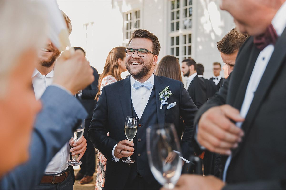Hochzeitsfoto von Bräutigam bei Sektempfang während Hochzeit auf Schloss Neuhardenberg - Schloss Neuhardenberg Hochzeitsfotograf © www.hochzeitslicht.de