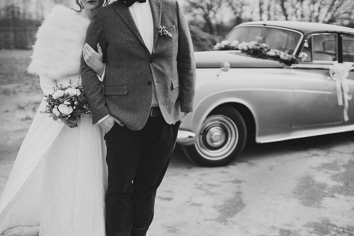 schwarz-weiß Hochzeitsfoto von Brautpaar mit Oldtimer-Hochzeitsauto bei Winterhochzeit in Berlin - Winterhochzeit Berlin-Pankow Hochzeitsfotograf © www.hochzeitslicht.de
