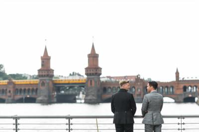 Paarfoto von Bräutigamen vor Oberbaumbrücke bei schwuler Hochzeit - Spreespeicher Berlin Hochzeitsfotograf © www.hochzeitslicht.de