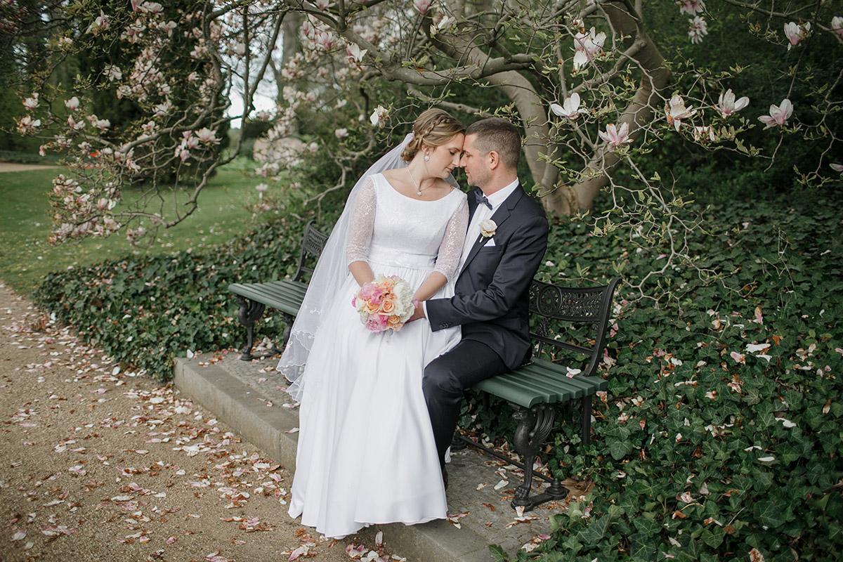 Brautpaarfoto im Park vor Magnolienbaum bei Frühlingshochzeit - Löwenpalais Berlin Hochzeitsfotograf © www.hochzeitslicht.de