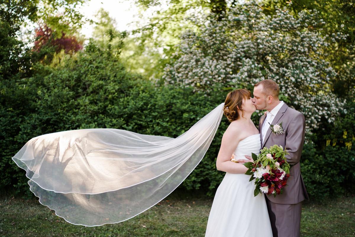 Idee Hochzeitsfoto Brautpaar wehender Schleier - Dorfkirche Britz Hochzeitsfotograf © www.hochzeitslicht.de