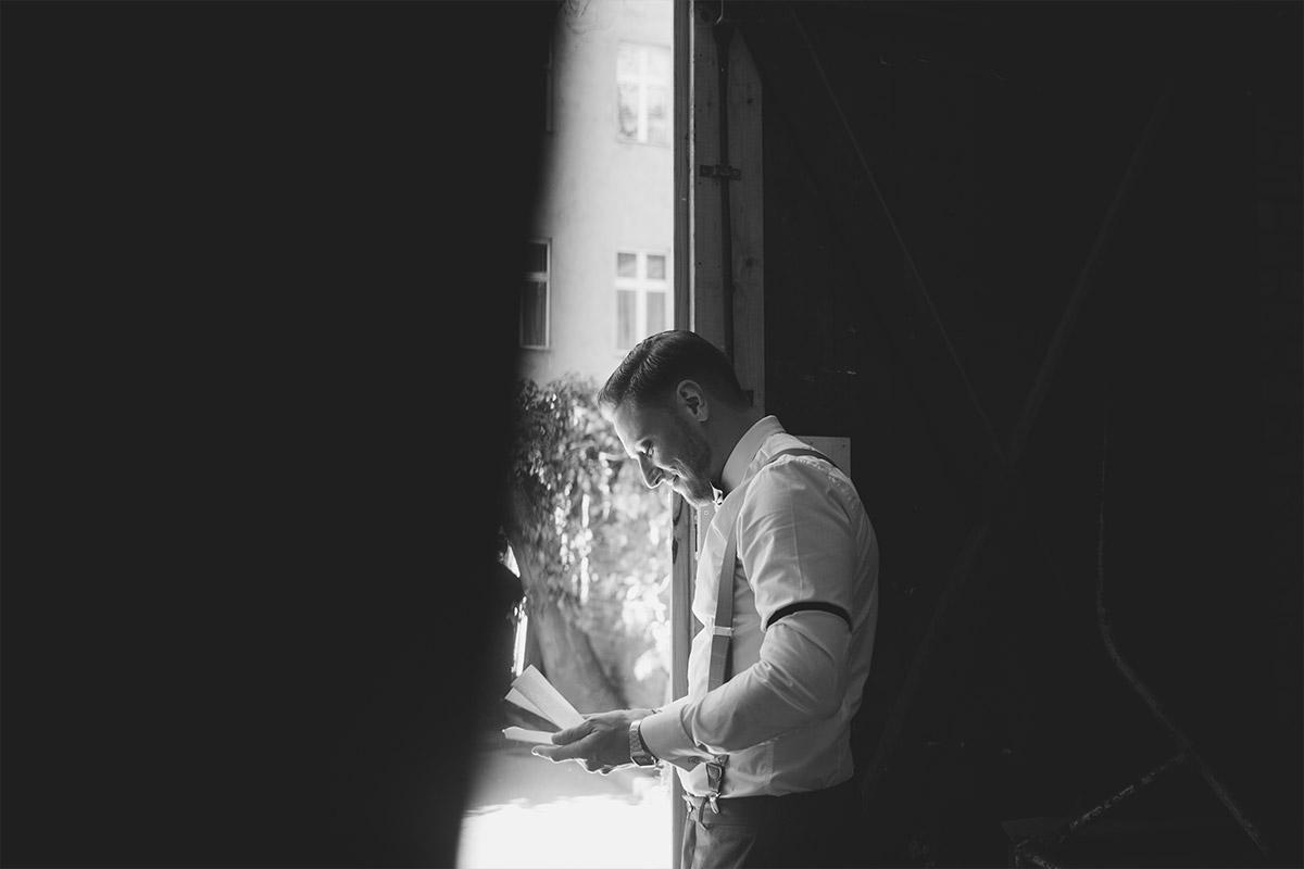 ungestelltes Hochzeitsfoto von Bräutigam beim Lesen eines Liebesbriefs am Hochzeitstag bei Vintage-Hochzeit in Alter Schmiede - Old Smithy's Dizzle Hochzeitsfotograf Berlin © www.hochzeitslicht.de