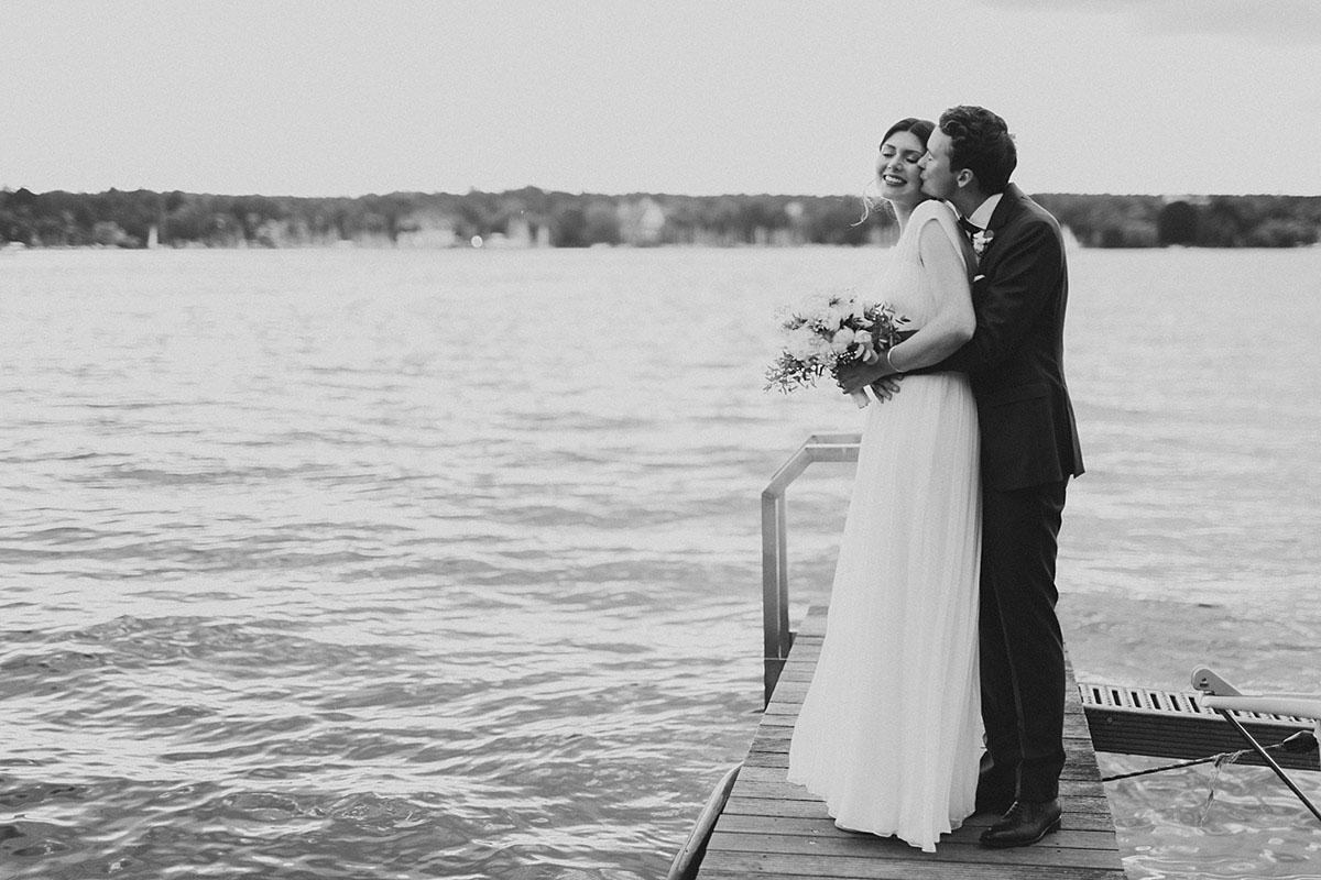 inniges Hochzeitsfoto von Brautpaar auf Bootssteg am Wannsee - Gästehaus Villa Blumenfisch am Großen Wannsee Berlin Hochzeitsfotograf © www.hochzeitslicht.de