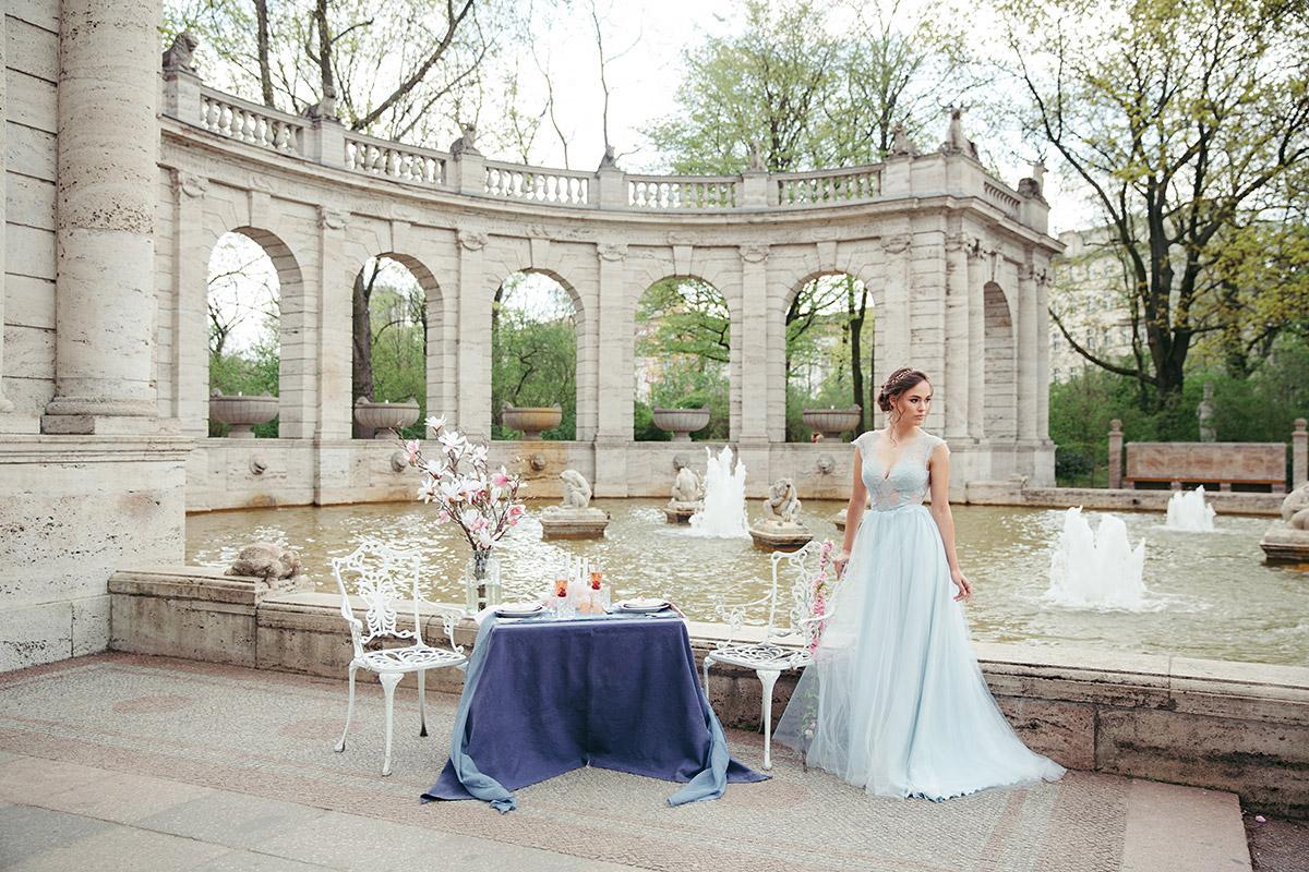 Hochzeitsfoto von Braut an table for two mit frühlingshafter Dekoration an Brunnen in Berliner Park - Editorial Shooting Magnolie Frühlingshochzeit Berlin © www.hochzeitslicht.de