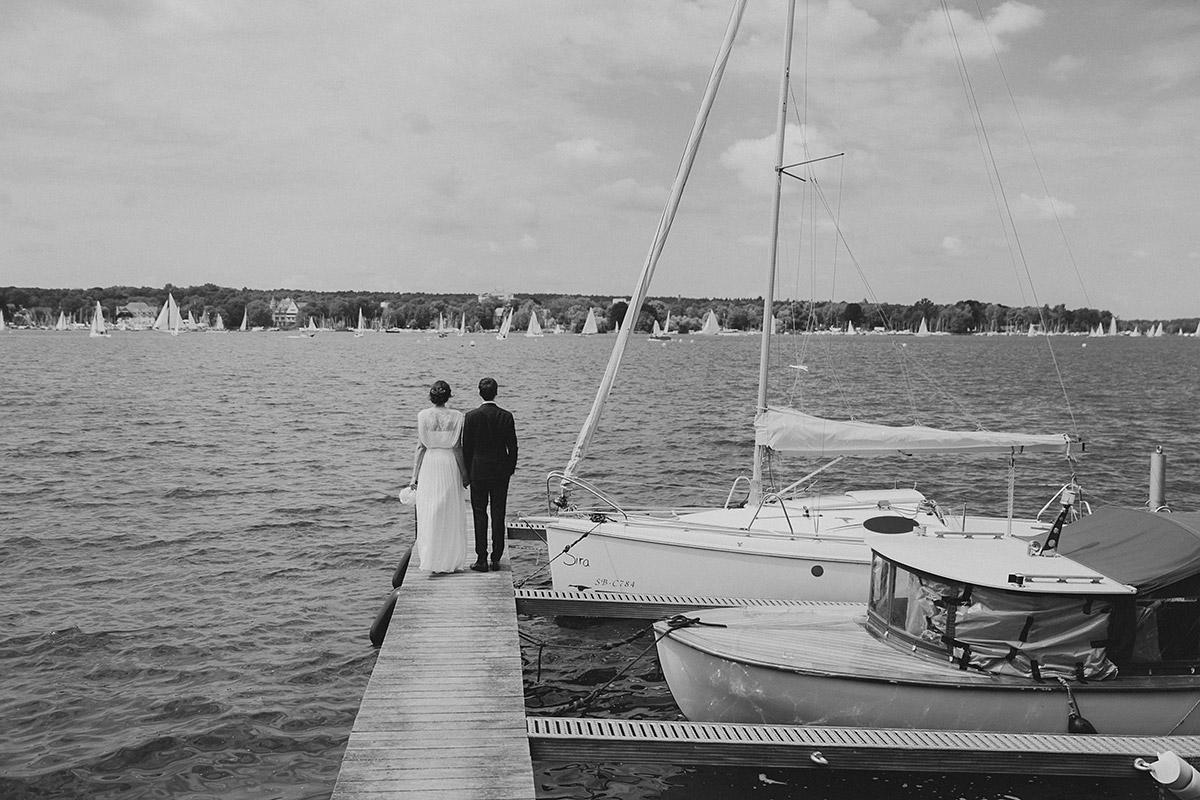 schwarz-weiß Hochzeitsfotografie von Braut und Bräutigam auf Bootsteg am Ufer des Wannsee - Gästehaus Villa Blumenfisch am Großen Wannsee Berlin Hochzeitsfotograf © www.hochzeitslicht.de