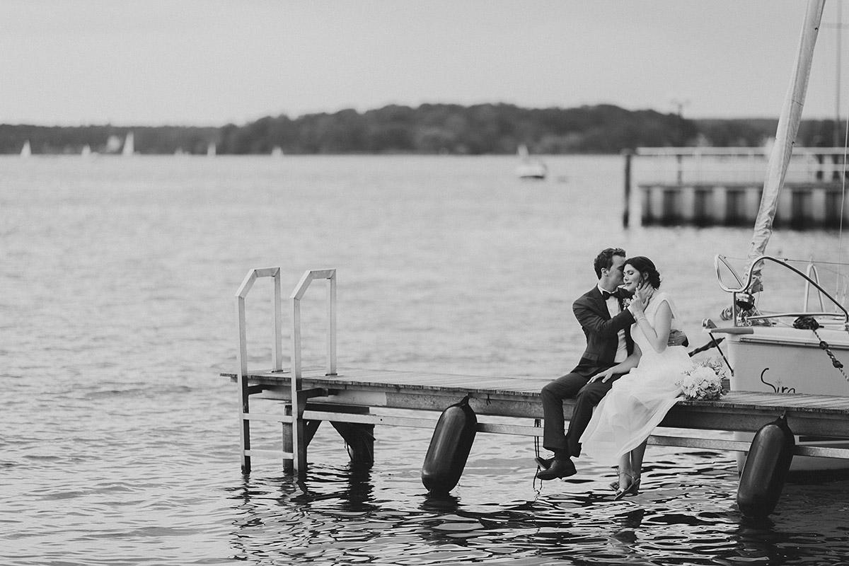 romantische schwarz-weiß Hochzeitsfotografie von Brautpaar auf Bootssteg am Wannsee - Gästehaus Villa Blumenfisch am Großen Wannsee Berlin Hochzeitsfotograf © www.hochzeitslicht.de