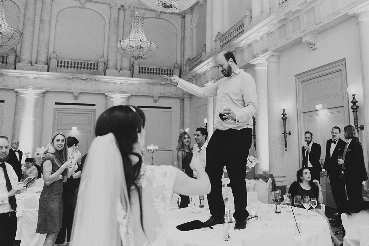 Gast tanzt bei Hochzeitsfeier auf dem Tisch - Hotel de Rome Berlin Hochzeitsfotograf © www.hochzeitslicht.de