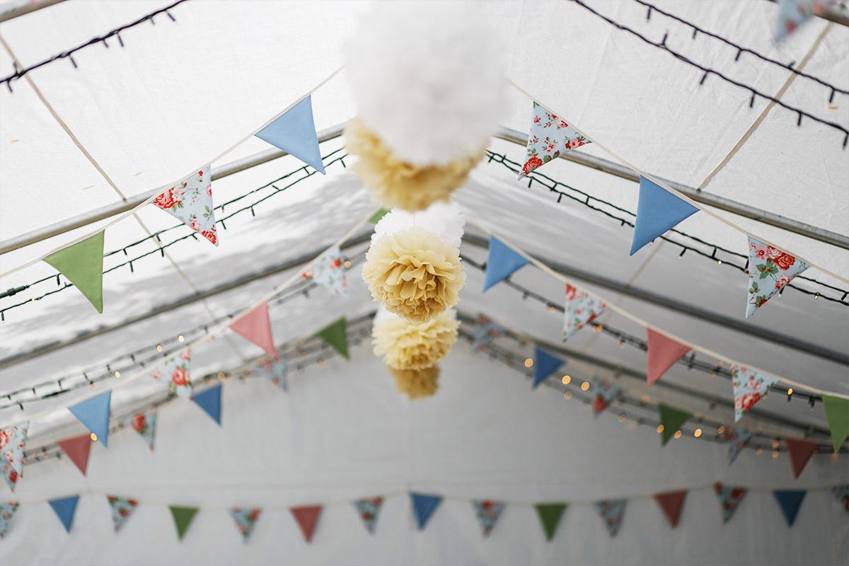 Detailfoto von Pompoms und Wimpelgirlanden als Schmuck für Zelt bei Gartenhochzeit - Standesamt Rathaus Schmargendorf Berlin Hochzeitsfotograf © www.hochzeitslicht.de