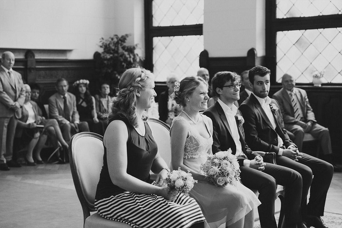 Hochzeitsreportagefoto von Brautpaar, Trauzeugen und Gästen bei Trauung - Standesamt Rathaus Schmargendorf Berlin Hochzeitsfotograf © www.hochzeitslicht.de