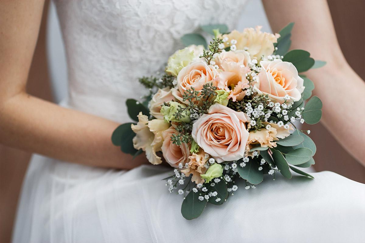 modernes Hochzeitsfoto von Braut mit Fokus auf Brautstrauß aus lachsfarbenen Rosen, Blumen in Pastelltönen, Eukalyptus und Schleierkraut - Seelodge Kremmen Hochzeitsfotograf © www.hochzeitslicht.de