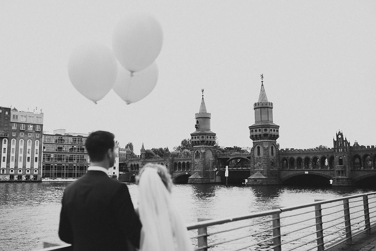 schwarz-weiß Hochzeitsfoto von Brautpaar mit Luftballons an Oberbaumbrücke - Berlin Friedrichshain Hochzeitsfotograf © www.hochzeitslicht.de