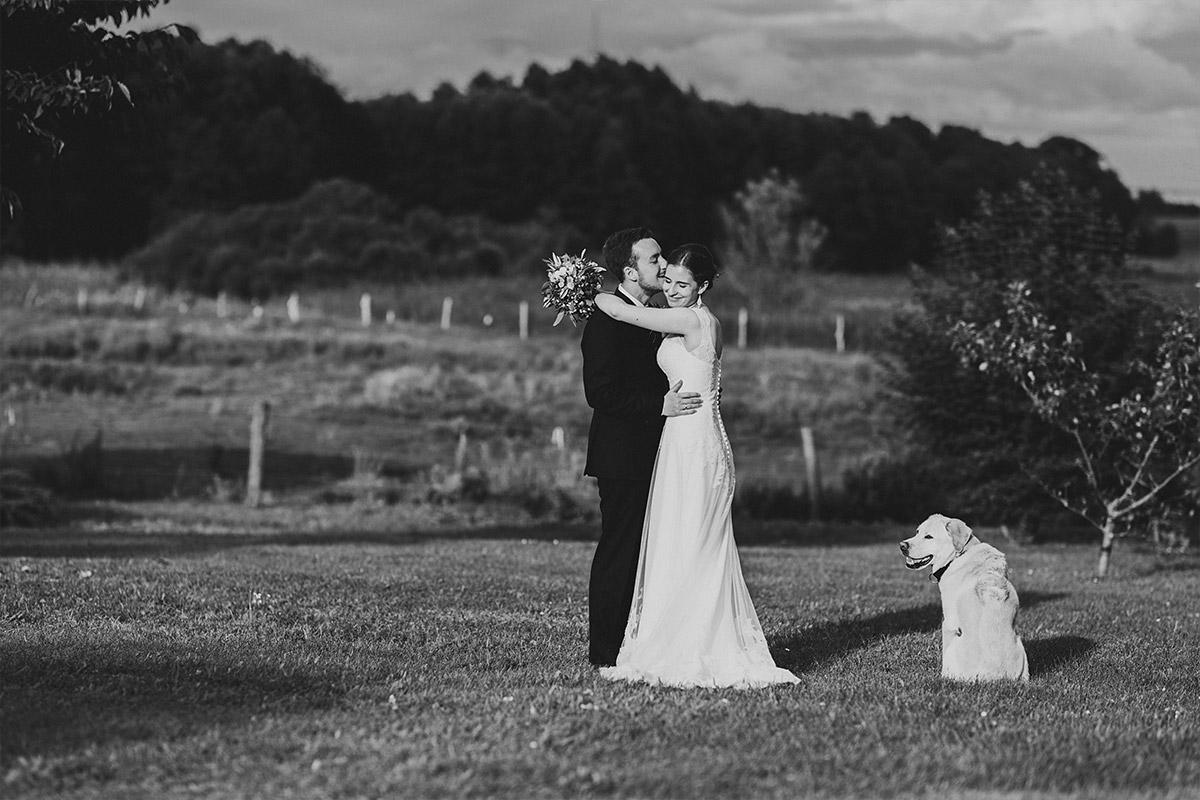 romantisches Hochzeitsfoto von Brautpaar mit Hund im Grünen - Landhaus Garzau Märkische Schweiz Hochzeitsfotograf © www.hochzeitslicht.de