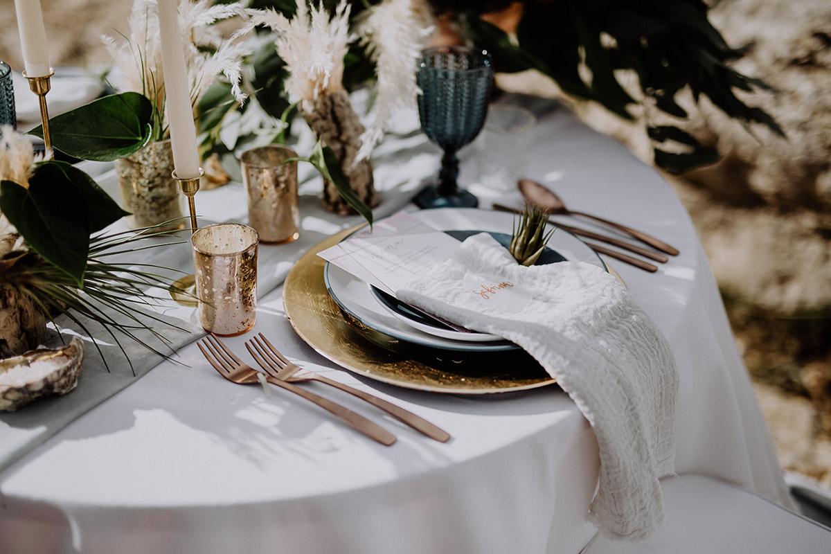 Tischdekoration mit Muscheln, Gräsern und Treibholz bei Hochzeit am Meer - Mallorca Hochzeitsfotograf © www.hochzeitslicht.de