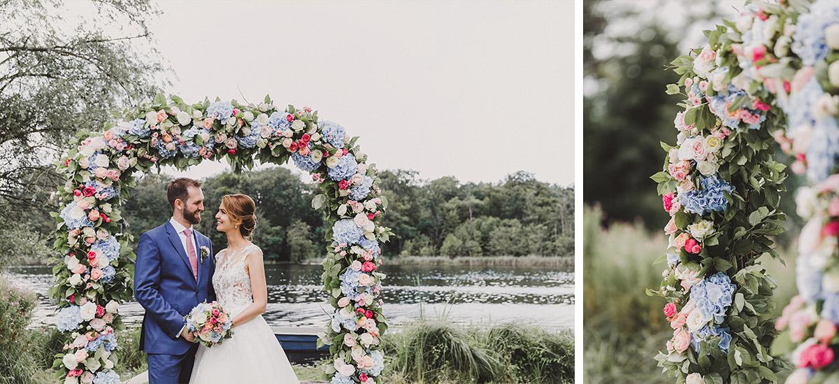 Brautpaarfoto unter Blumenbogen am See - Landgut Stober Hochzeitsfotograf © www.hochzeitslicht.de