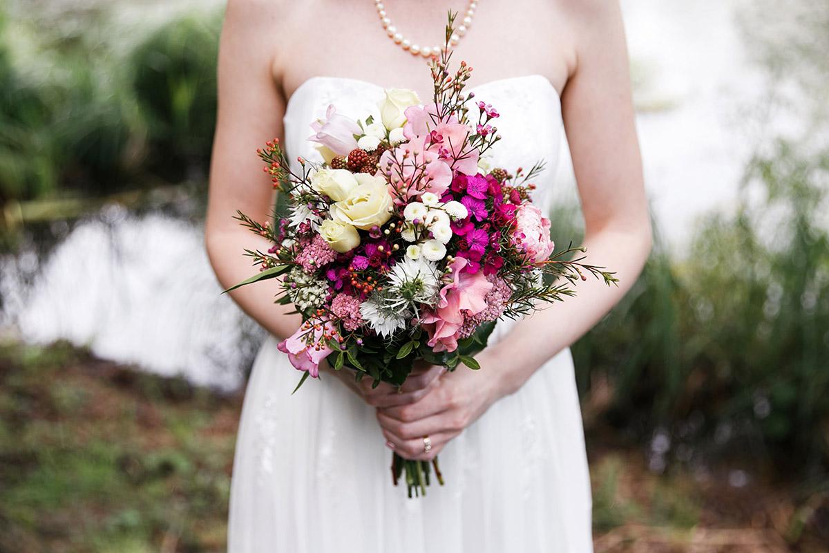 Braut mit sommerlichem Brautstrauß in pink und Pastelltönen - Seelodge Kremmen Hochzeitsfotograf © www.hochzeitslicht.de
