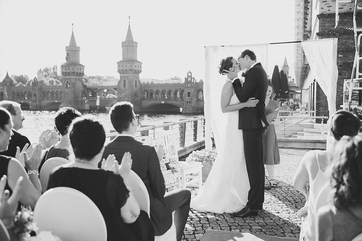 Hochzeitsfoto von Kuss bei Ja-Wort bei freier Trauung an Spree mit Blick auf Oberbaumbrücke - Spreespeicher Hochzeitsfotograf © www.hochzeitslicht.de
