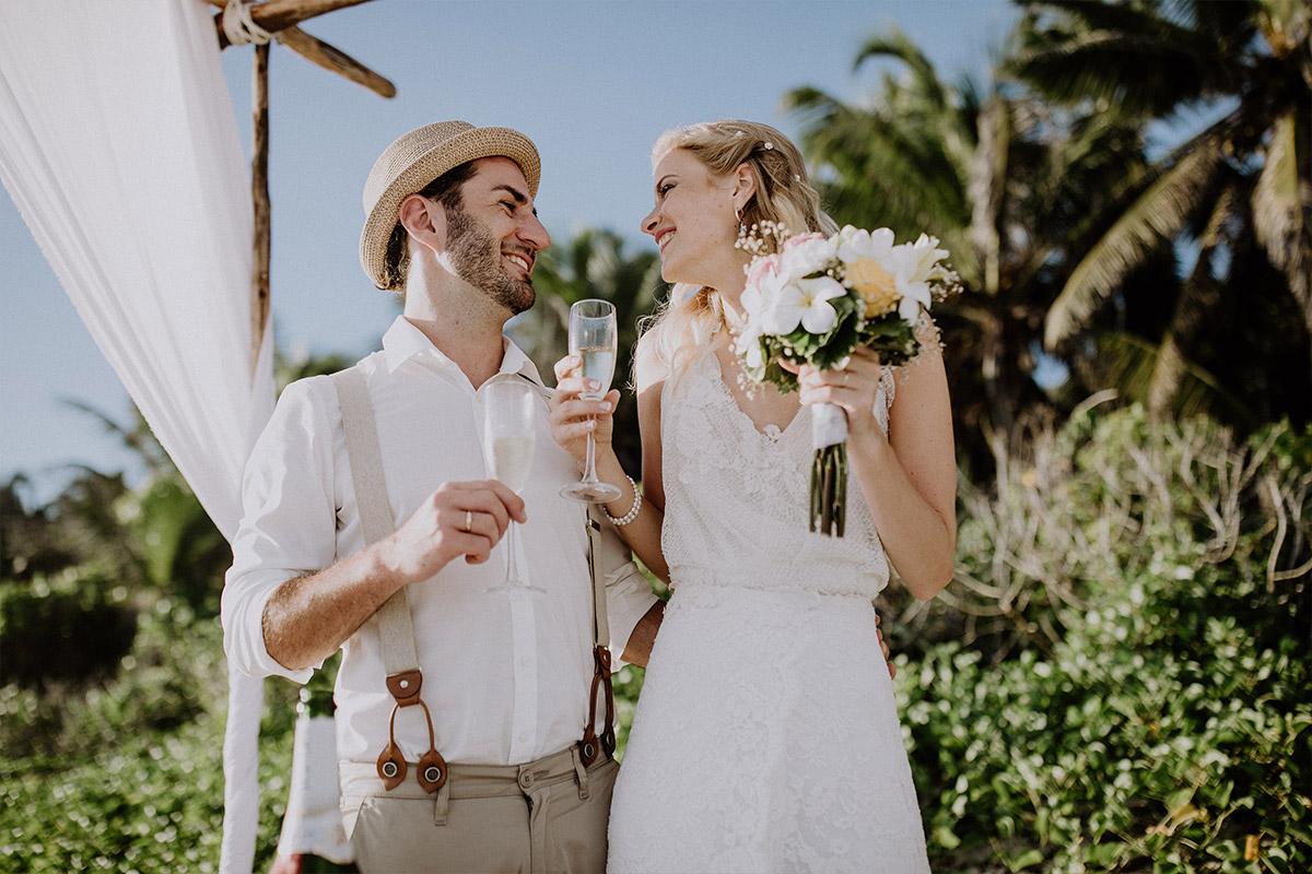 Brautpaar beim Anstoßen nach Trauung am Meer - Strandhochzeit Seychellen Hochzeitsfotograf © www.hochzeitslicht.de