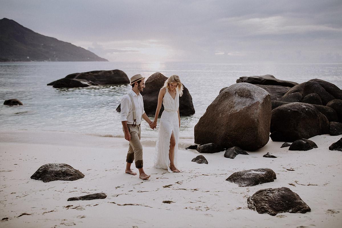 Brautpaar bei romantischem Strandspaziergang - Strandhochzeit Seychellen Hochzeitsfotograf © www.hochzeitslicht.de