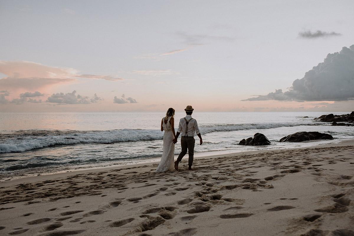 romantisches Hochzeitsfoto von Brautpaar bei Strandspaziergang - Strandhochzeit Seychellen Hochzeitsfotograf © www.hochzeitslicht.de