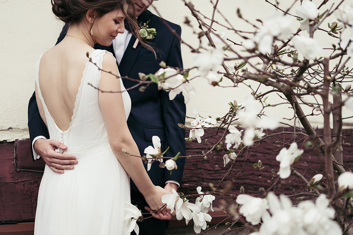 Hochzeitsfoto Brautpaar bei Scheunenhochzeit mit blühender Magnolie - Ferienscheune Barnimer Feldmark Hochzeitsfotograf © www.hochzeitslicht.de