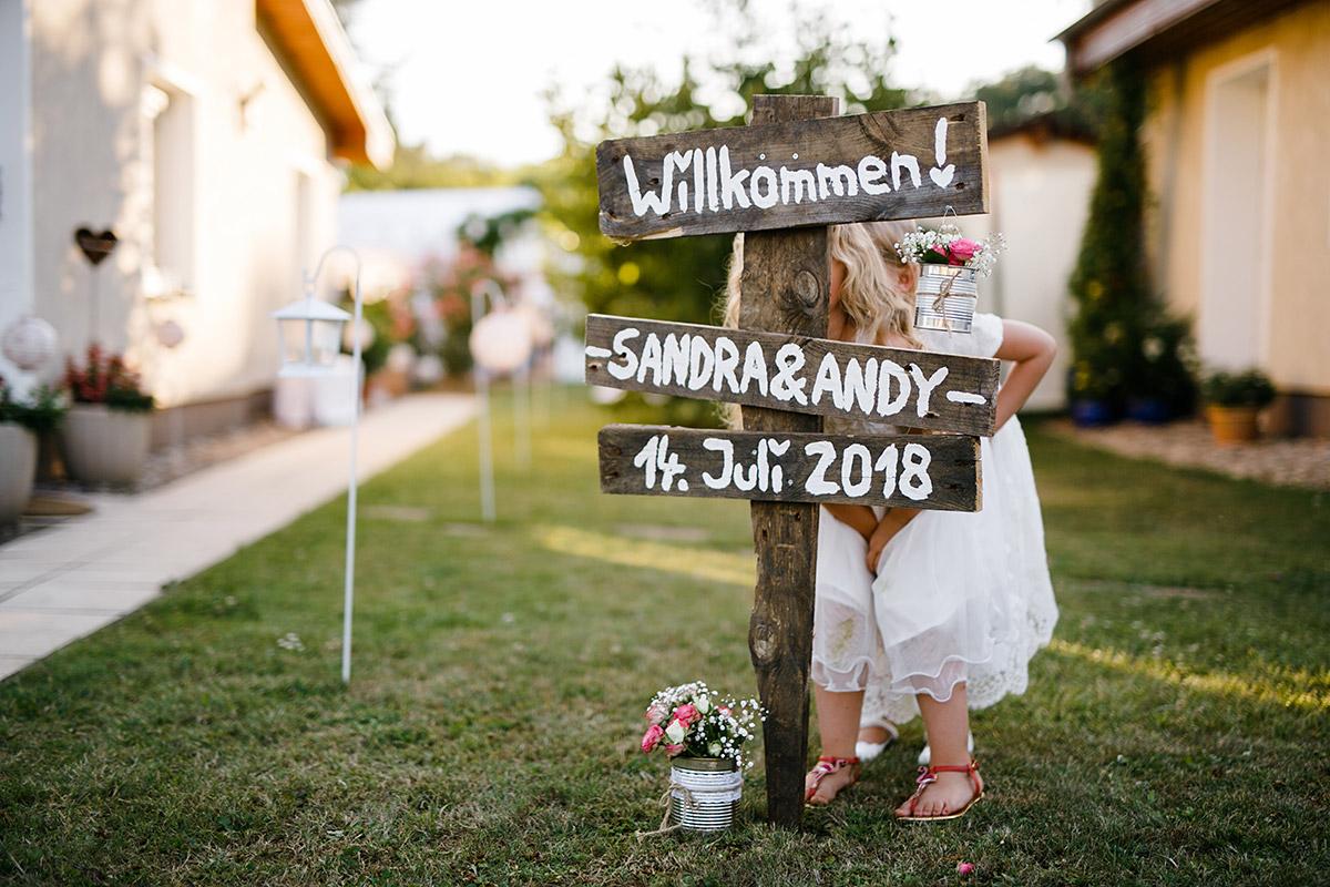 kleine Hochzeitsgäste verstecken sich hinter DIY Willkommen Holzschild - Gartenhochzeit Berlin Hochzeitsfotograf © www.hochzeitslicht.de