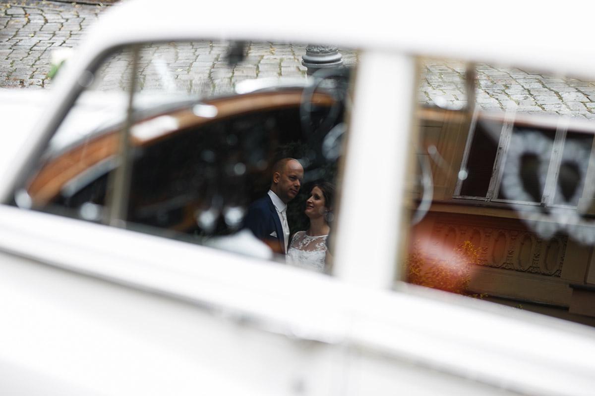 künstlerisches Brautpaarfoto Reflektion in weißem Hochzeitsauto - Hochzeitsvilla Zehlendorf Hochzeitsfotograf © www.hochzeitslicht.de