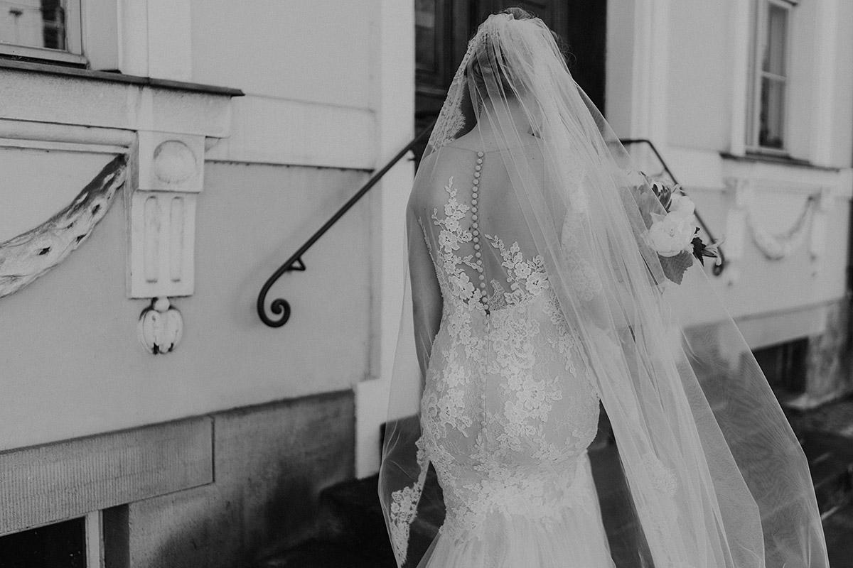 schwarz-weiß Hochzeitsfoto Braut von hinten Pronovias Brautkleid mit tiefem Rückenausschnitt und Spitze im Meerjungfrauenschnitt - Schloss Glienicke Hochzeitsfotograf Potsdam © www.hochzeitslicht.de