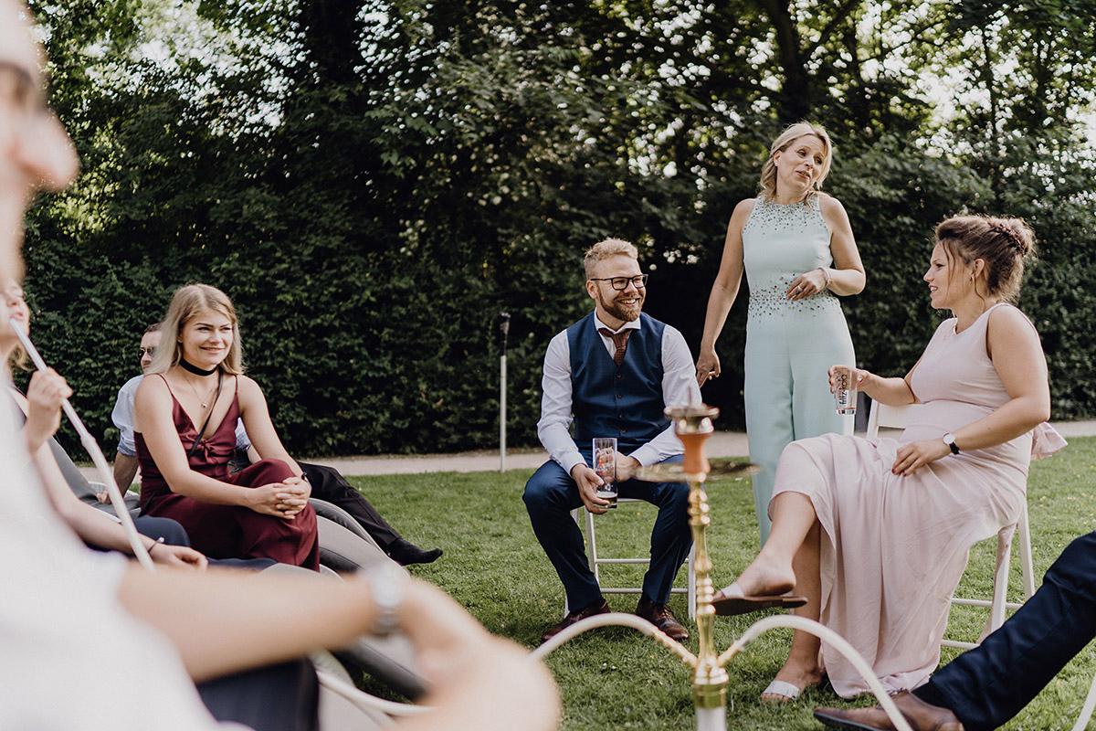 Hochzeitsreportagefoto von Gästen im Garten bei Hochzeitsfeier - Villa Blumenfisch Berlin Hochzeitsfotograf © www.hochzeitslicht.de
