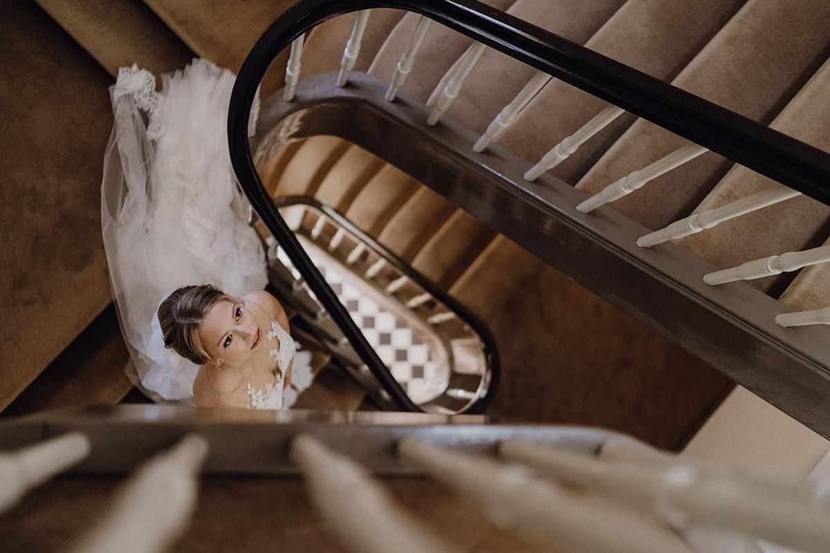 Braut auf schöner Treppe mit Pronovias Brautkleid mit Schleppe - Schloss Glienicke Hochzeitsfotograf Potsdam © www.hochzeitslicht.de