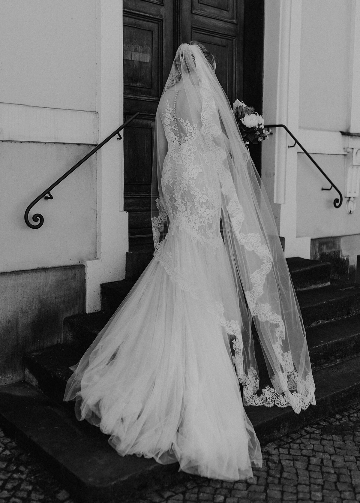 schwarz-weiß Hochzeitsfoto Braut in Pronovias Brautkleid mit langer Schleppe und langem Spitzenschleier - Schloss Glienicke Hochzeitsfotograf Potsdam © www.hochzeitslicht.de