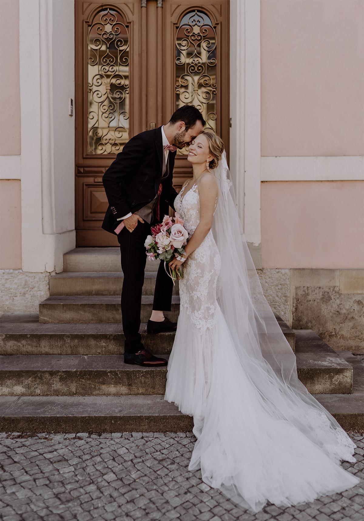 verspieltes Brautpaarfoto vor rosa Hausfassade - Schloss Glienicke Hochzeitsfotograf Potsdam © www.hochzeitslicht.de