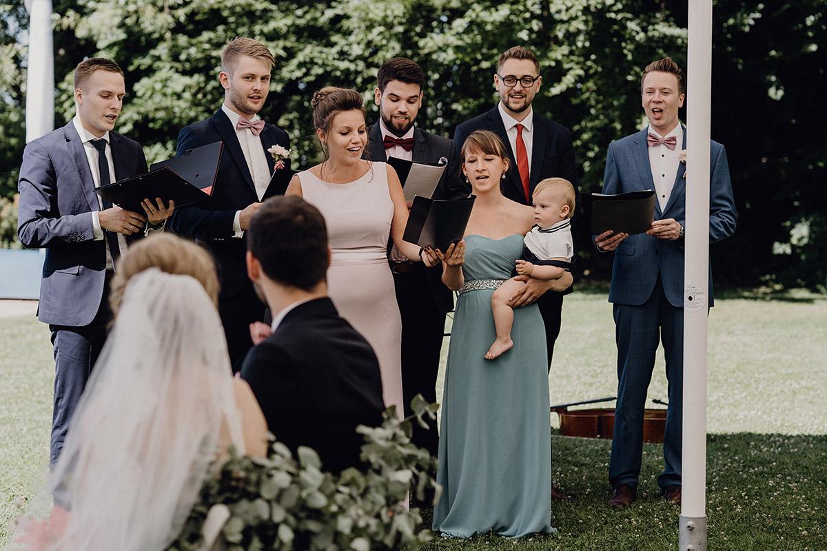 Hochzeitsreportagefoto singende Gäste bei Trauung im Garten - Villa Blumenfisch Berlin Hochzeitsfotograf © www.hochzeitslicht.de